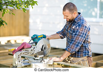 Carpenter Cutting Wood Using Table Saw At Construction Site...