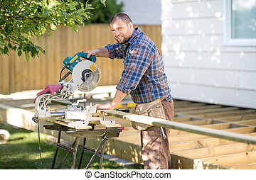 Carpenter Cutting Wood Using Table Saw At Site - Portrait of...