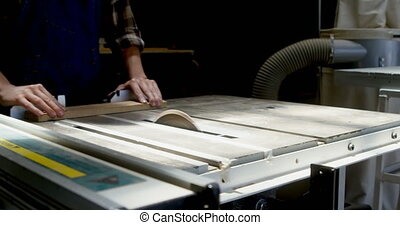 Carpenter cutting wooden plank on wooden saw machine 4k - ...