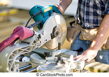 Carpenter Cutting Wooden Plank With Table Saw At Site