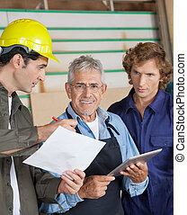 Carpenter Discussing With Colleagues In Workshop