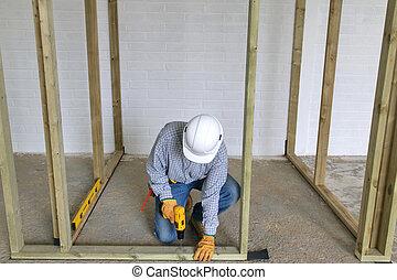 Carpenter fixing a timber framework into a concrete floor