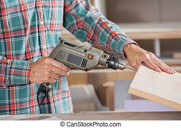 Carpenter Drilling Wooden Plank At Workshop