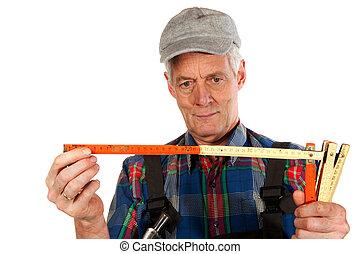 Carpenter - Elderly carpenter is measuring in portrait on...