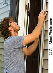 Carpenter Fixing Door - a young, attractive carpenter is ...