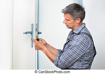 Carpenter Fixing Lock In Door With Screwdriver - Male...