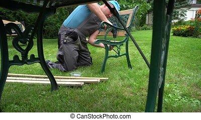 Carpenter guy disassemble retro bench. Outdoor furniture ...