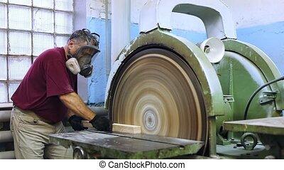 Carpenter handles wooden block on grinding machine - Worker ...