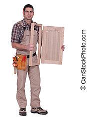 carpenter holding a wooden window frame