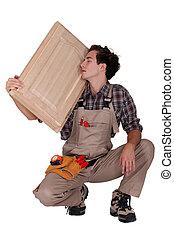 carpenter holding a wooden window