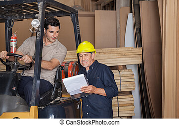 Carpenter Holding Clipboard By Colleague In Forklift