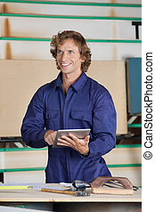 Carpenter Holding Digital Tablet While Looking Away