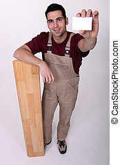 Carpenter holding up his business card