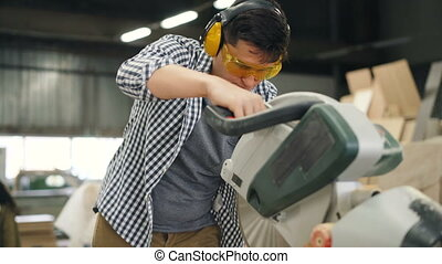Carpenter young man in safety goggles and headphones is working with electric saw in workshop making handmade furniture. People and equipment concept.
