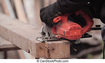 Carpenter in work clothes and gloves neatly cuts piece of board with circular electric saw and strokes wood with hand, close-up view in slow motion. Flying sawdust of working circular. Cutting grinder