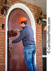 carpenter installing lock at big metal door