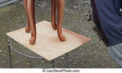 Carpenter is covering stool by lacquer