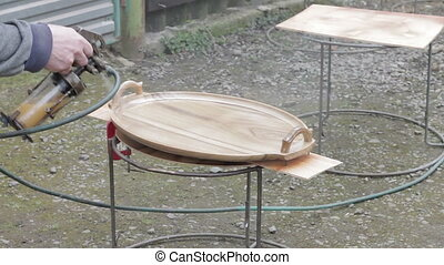 Carpenter is covering wooden platter by lacquer