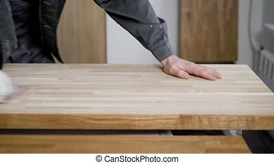 carpenter is processing timber planks, grinding by abrasive paper, rubbing it over surface, close-up of hands
