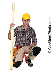 carpenter kneeling with plank of wood