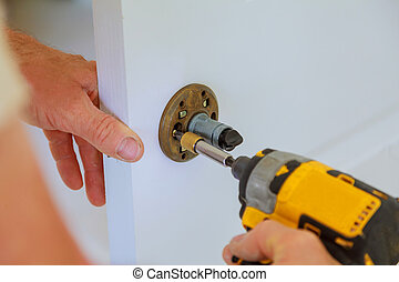 carpenter lock installation with electric drill into interior wood door