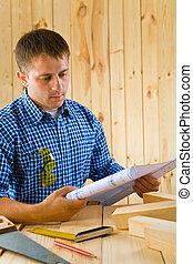 carpenter looks on the blueprint