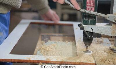 Carpenter manufacturing furniture drilling a hole