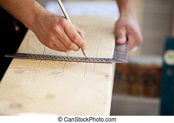 Carpenter marking a wooden beam