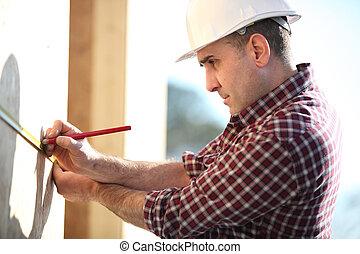 Carpenter marking wooden panel