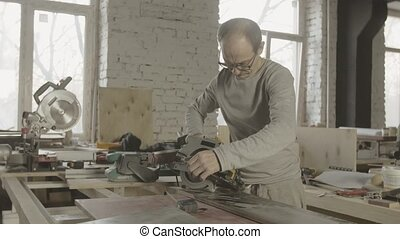 Carpenter measure wooden board by ruler, circular saw on table. Furniture