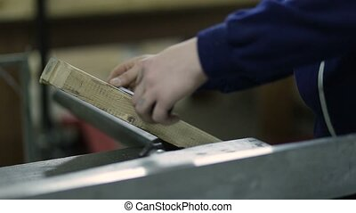 Carpenter measures length of plank before sawing