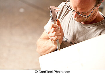carpenter measuring a board with calipers - focus on ...