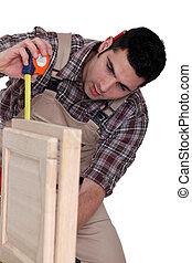 Carpenter measuring a piece of furniture