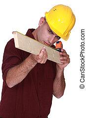 Carpenter measuring a piece of wood