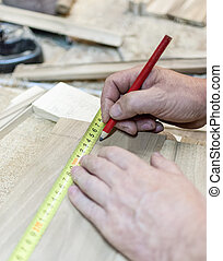Carpenter measuring a product with ruler