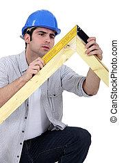 carpenter measuring a wooden frame
