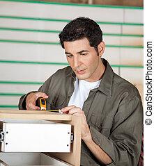 Carpenter Measuring Cabinet In Workshop