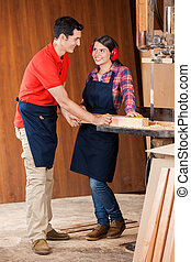 Carpenter Measuring Plank While Looking At Each Other