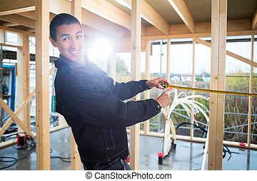 Carpenter Measuring Wood At Construction Site
