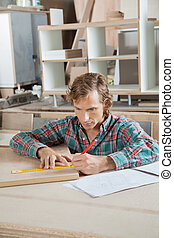 Carpenter Measuring Wood At Table