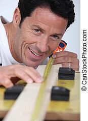 Carpenter measuring wood lath
