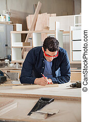 Carpenter Measuring Wood With Ruler And Pencil