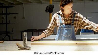 Carpenter measuring wooden plank in workshop 4k - Female ...