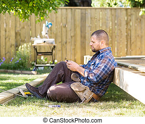 Carpenter Messaging On Cellphone While Leaning On Wooden Frame
