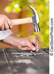 Carpenter nailing a nail