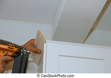 Carpenter nailing crown moldings in the kitchen cabinets...