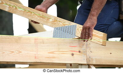 Carpenter lines up a roofing truss using a strait line and then nails it into position with a hammer.