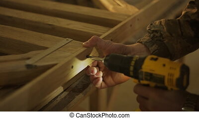 Carpenter or Joiner fastens a wooden product with screw and...