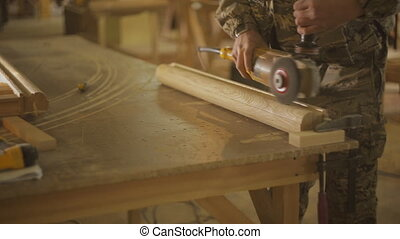 Carpenter or Joiner polishes a wooden part of furniture with...