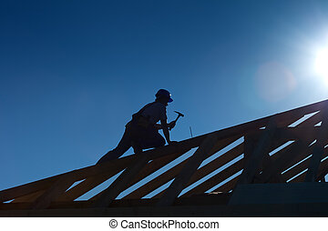 Carpenter or joiner working on top of the roof - Carpenter...